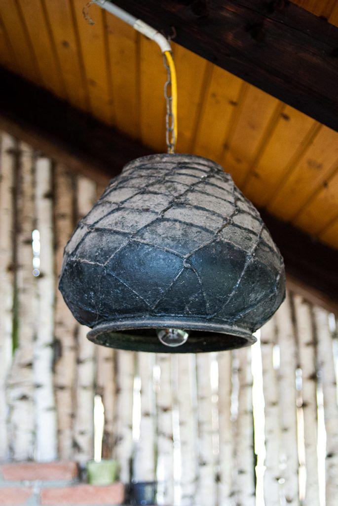 Črna posoda ovita z žico za kuhanje, sedaj predelana v luč.